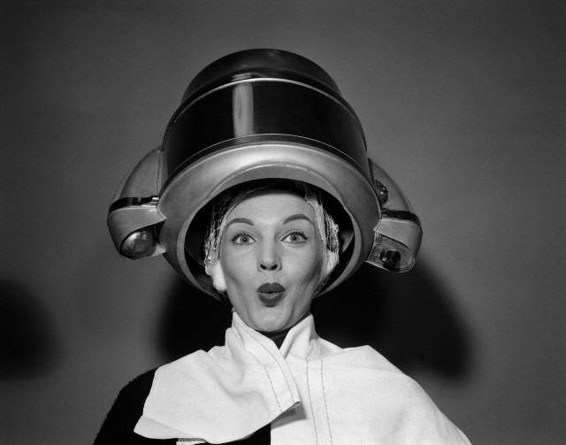 1950s woman under hair dryer with towel on shoulders and hair net looking at camera